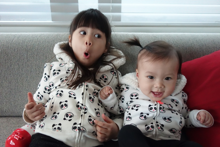 Isa and her big sister, Eva, in their matching hoodies before heading outside for some fun.